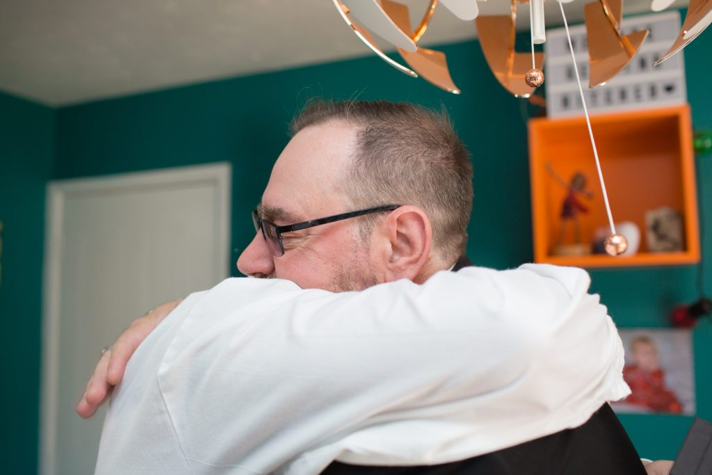 husband to be hugging his dad