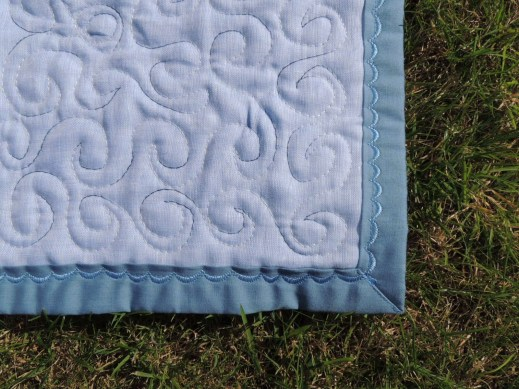 The quilt has been finished with a lovely decorative edge.