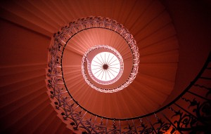 looking up into a large spiral staircase.
