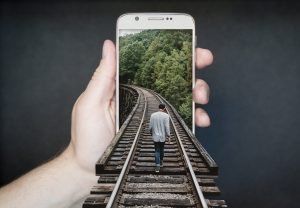 a man walking down a railroad track that leads into a smart phone being held in a hand - what track do you follow to learn how to live more consciously