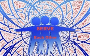 3 blue figures appearing as one simulating cooperation and mutual benefit by serving each other which is written across them in red. Behind them are multiple circles with words supporting cooperation