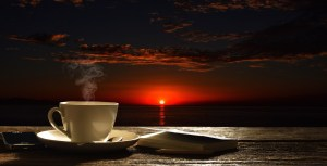 a cup of coffee sitting on a table overlooking a red sunset indicating a picture larger than the coffee alone