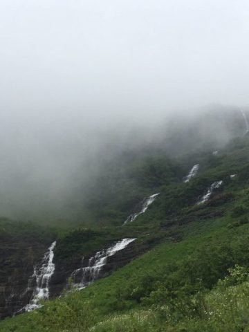 Green mountain side with waterfalls running down, ascending into clouds