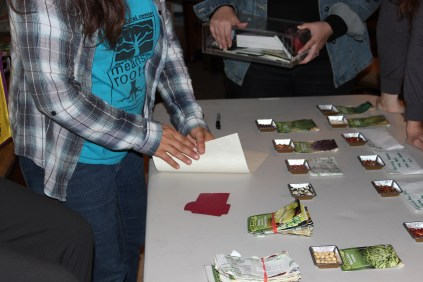 Giving a quick demonstration on how to make upcycled D.I.Y. seed envelopes for seed saving.