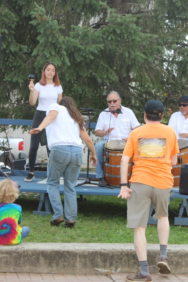 Raíces Cultural Center Ensemble Member Nicole Wines dancing piquetes in front of the drum.