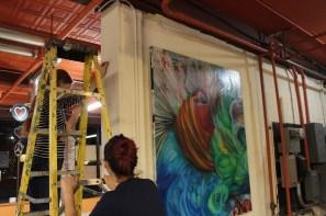 Veronica, owner of Tiger Art Supply, and volunteer Kira Herzog hanging artwork.