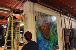 Veronica, owner of Tiger Art Supply, and volunteer Kira Herzog hanging artwork.