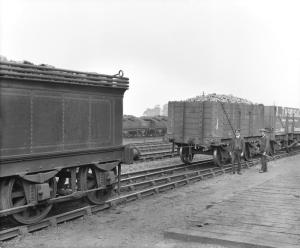 Railway engine towing wagons with a rope.