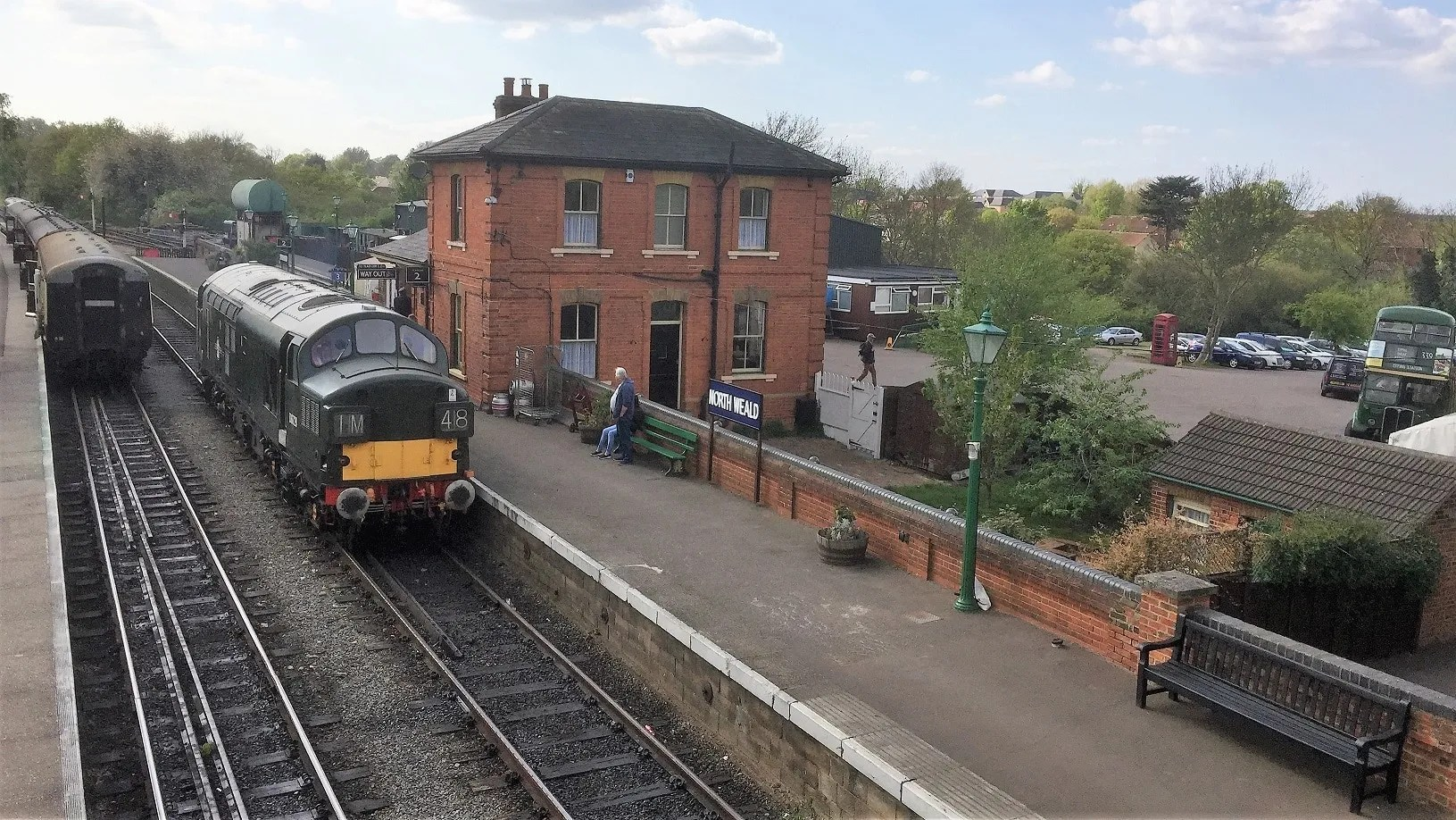 D6729 waits to depart from North Weald Station as London Transport country area RT1700 arrives on the Station forecourt