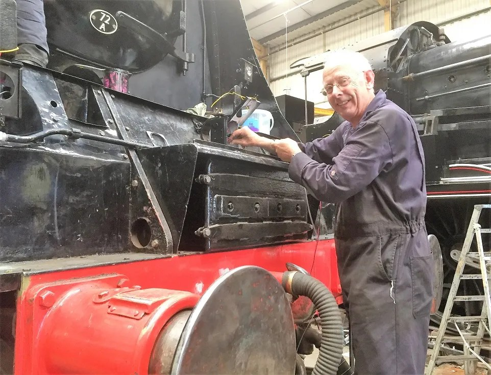 Geoff Rebey wiring up the newly fitted lights on 34072 at Herston Works
