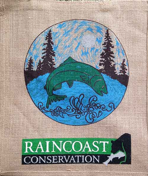 a sturdy burlap bag with a design of a salmon jumping in front of some coastal trees and the raincoast logo