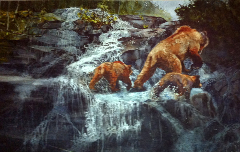 A family of grizzlies crosses a waterfall