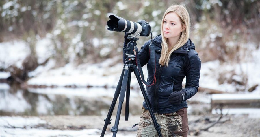 Colleen Gara, photographer, standing with your telephoto lens and her tripod.