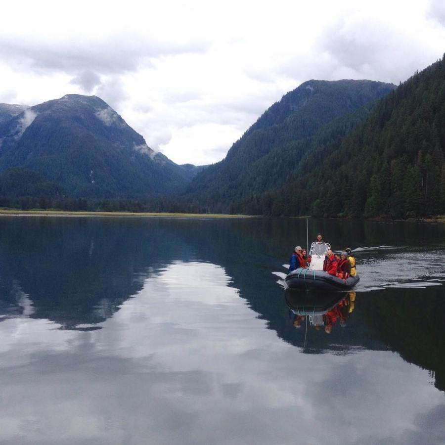 Raincoast staff approaching the Achiever boat on a red and white zodiac with mountains in the background reflected in the ocean waters
