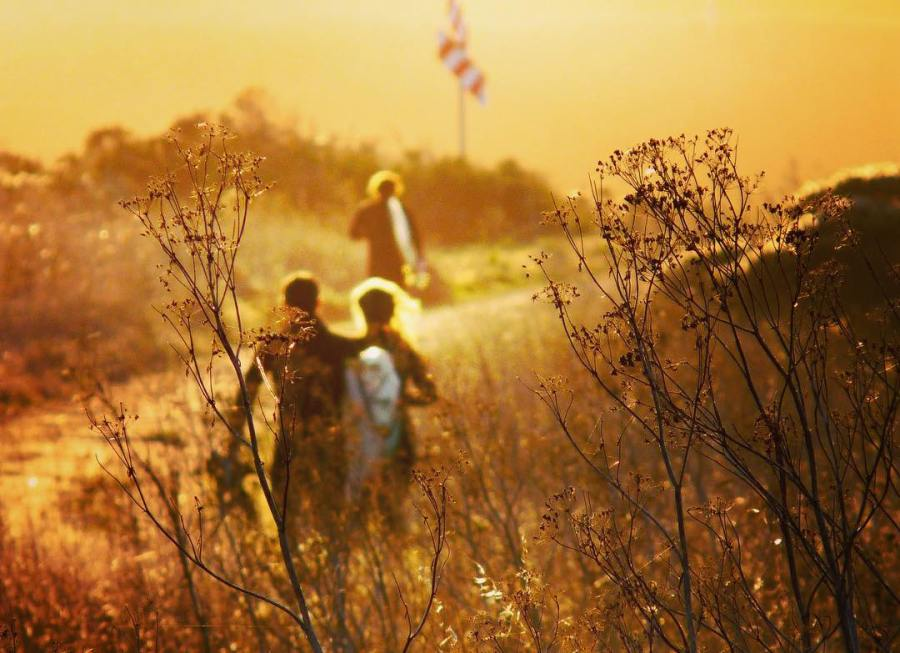 A sepia toned image of three backpackers walking amidst grass