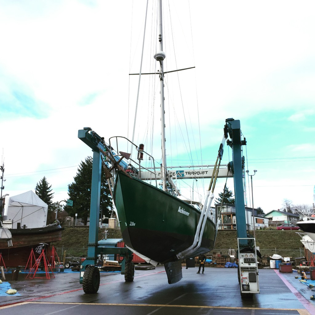 "A green boat suspended on ropes that make a cradle between two metal brackets. White writing on the side saying ""Achiever."""