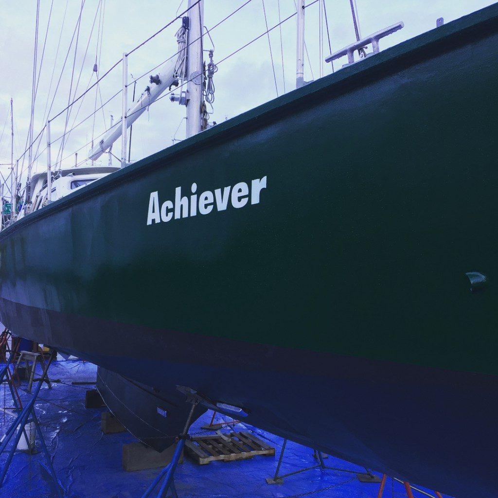 "A green boat lifted over a blue tarp with white writing on the side saying ""Achiever."""