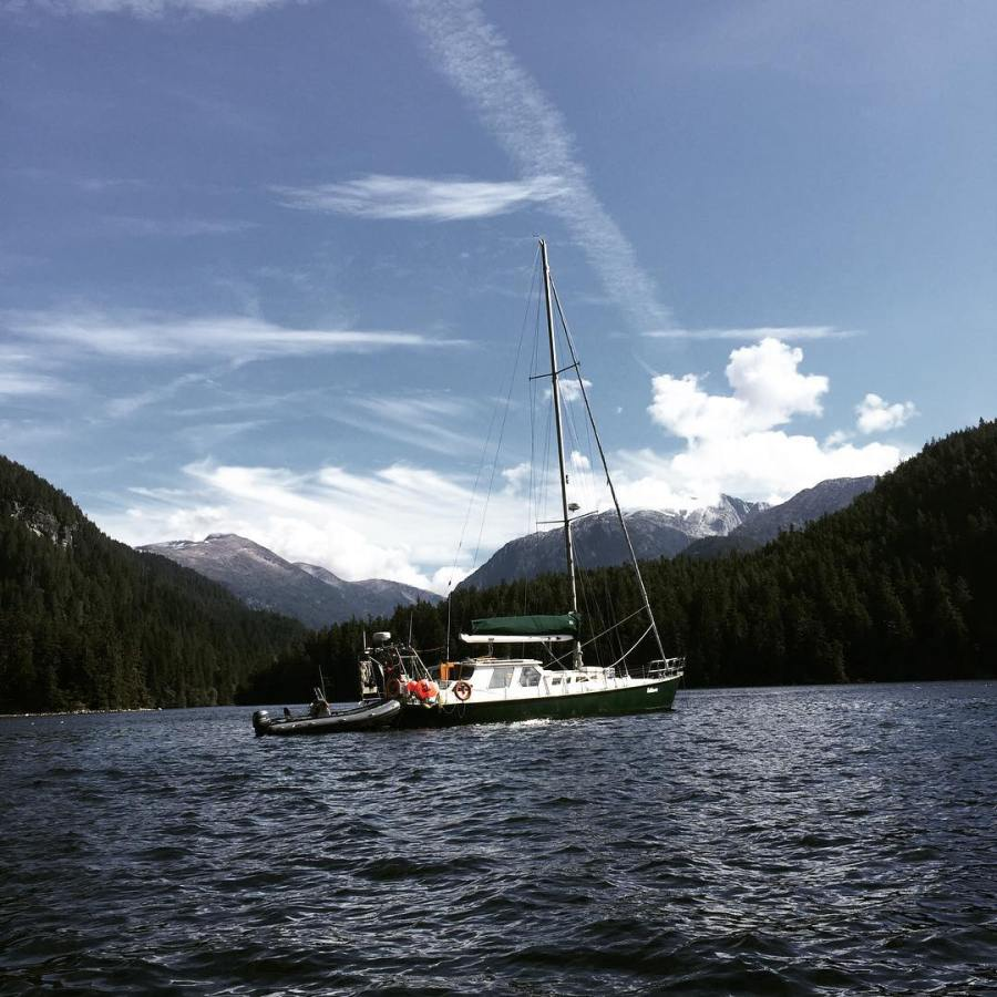 A green and white sailboat on the water with a hilly landscape in the distance.