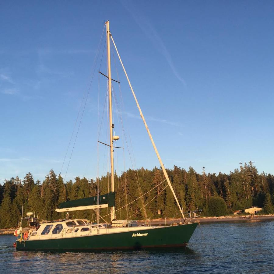 A green and white sailboat on the water with a forest in the background.