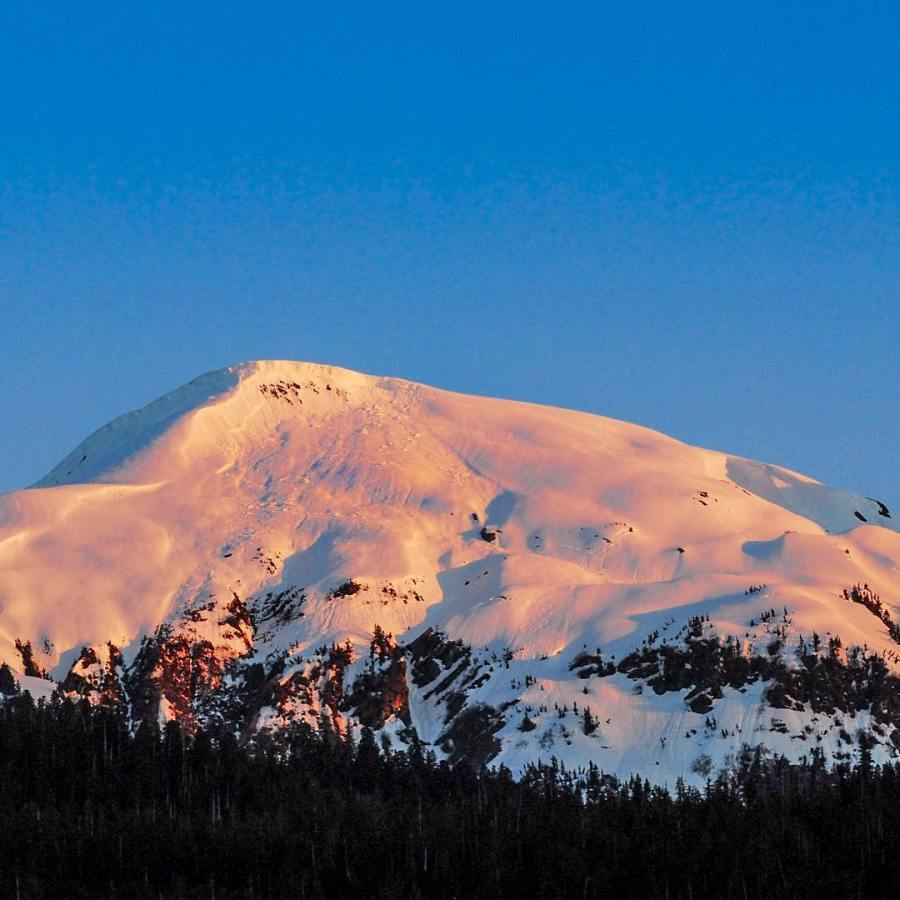 A snowy mountain against a blue sky tinted orange in the sunset.