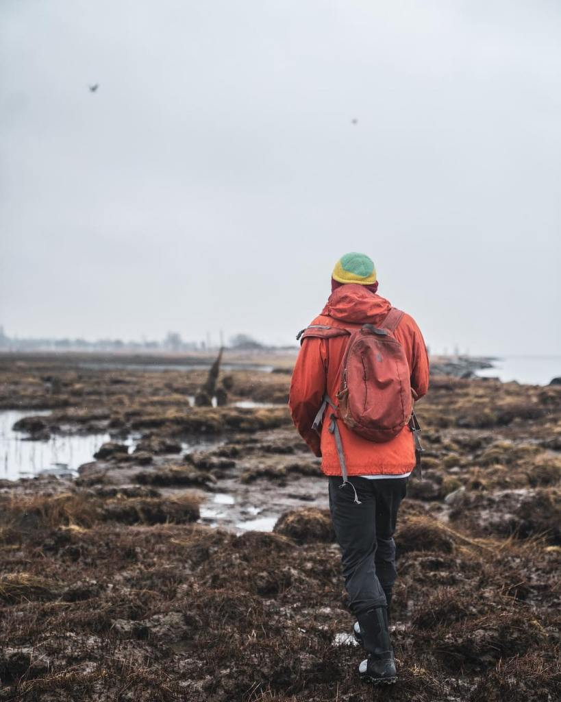 Someone in an orange jacket walking out along a rocky shore on a grey day.