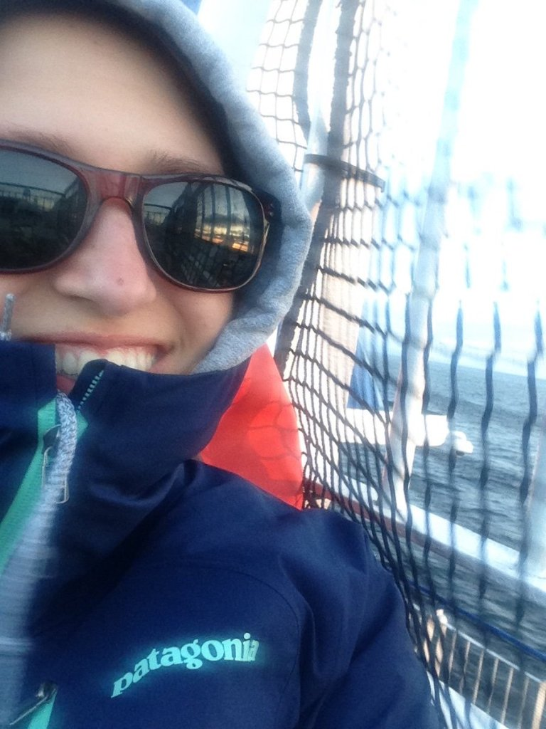 A blurry photo of a woman with hoodie and sunglasses smiling from behind her jacket.