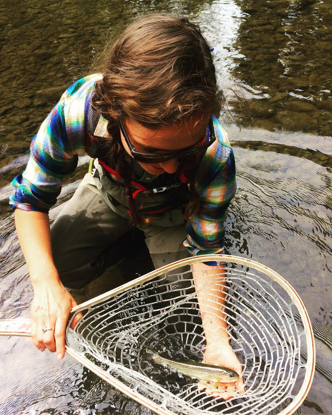 Woman in checked blue shirt and sunglasses kneels by the water holding a net with fish.