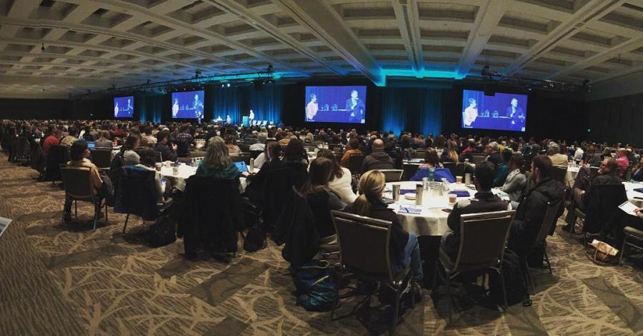 View of conference room from the back in dim lighting. Visible are backs of attendees's heads seated around round tables and three blue screens with indecipherable text and images on it, at the front of the room.