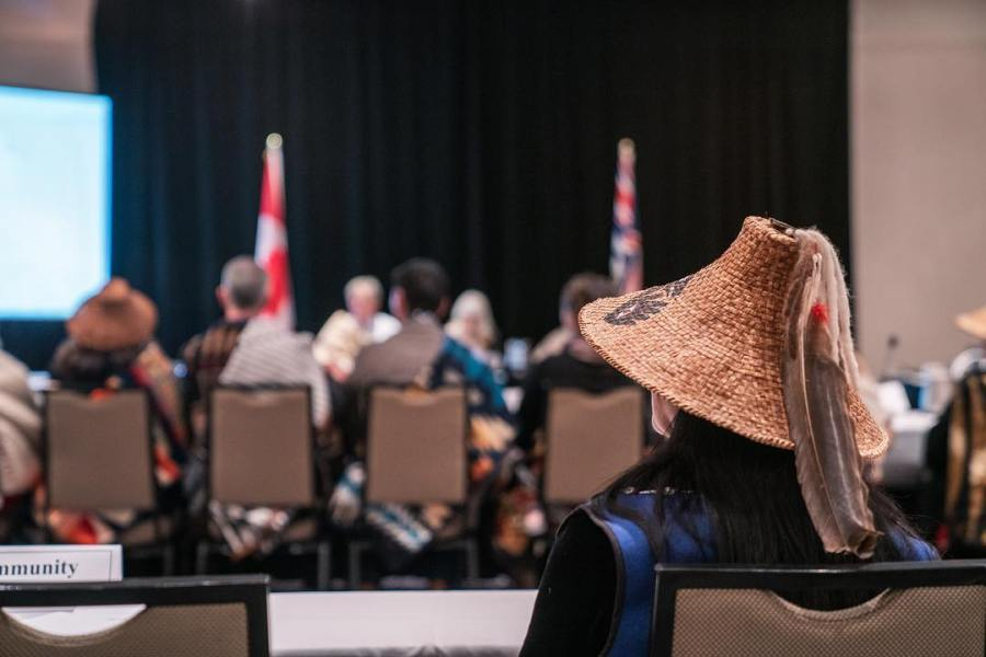 People sitting in chairs at the National Energy Board hearings about the Trans Mountain pipeline as a blurred background. In the foreground, there is the back of a person visible in blue wearing head gear