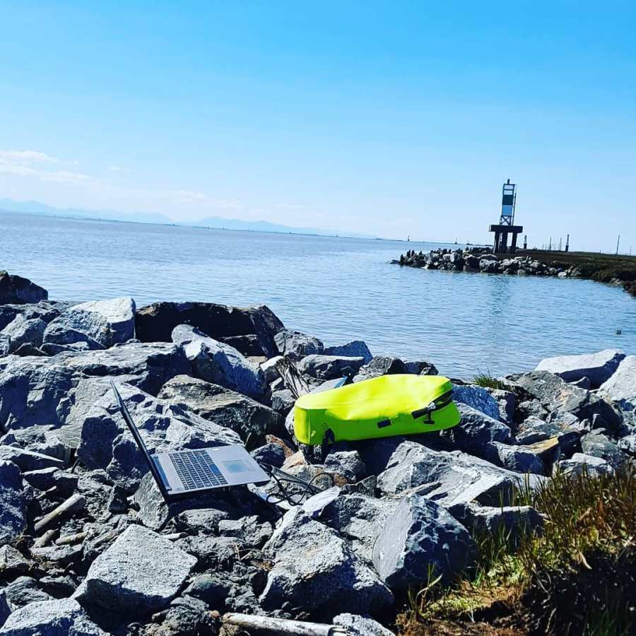 Laptop and flourescent yellow bag visible on the rocks near the Steveston jetty