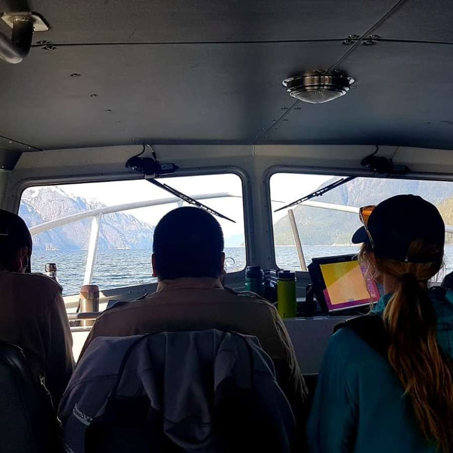 Heads and shoulders of three people visible from the back in a boat cockpit