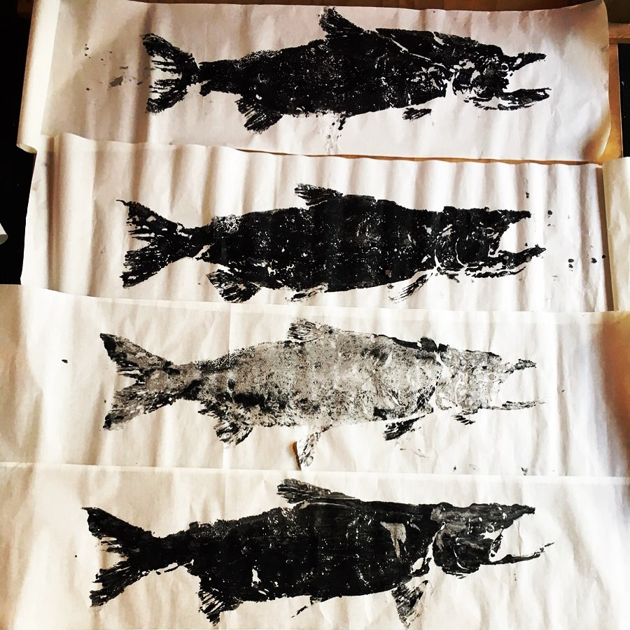 Four prints of salmon on white paper in varying shades of black and grey ranging from light to dark are arranged in a column.