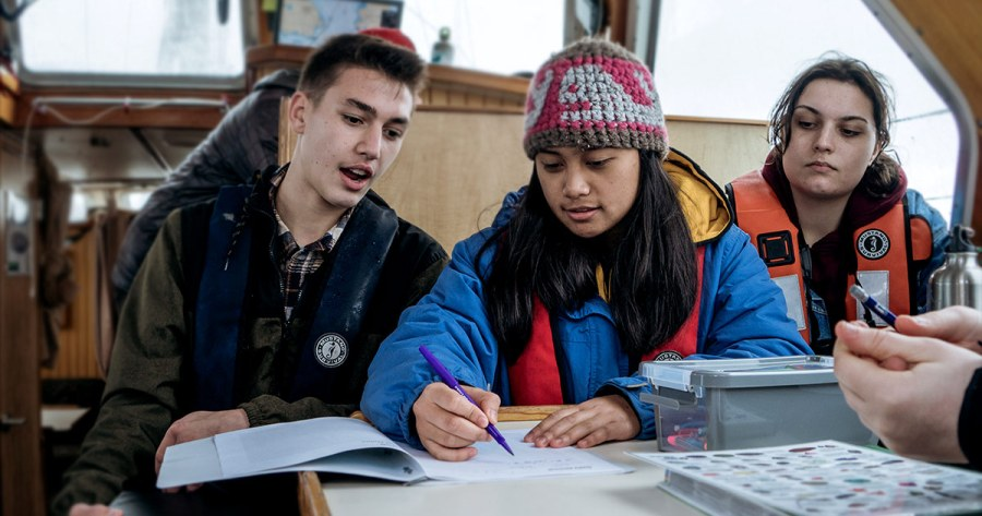 Students aboard Achiever look at the charts during the Salish Sea Emerging Stewards program.
