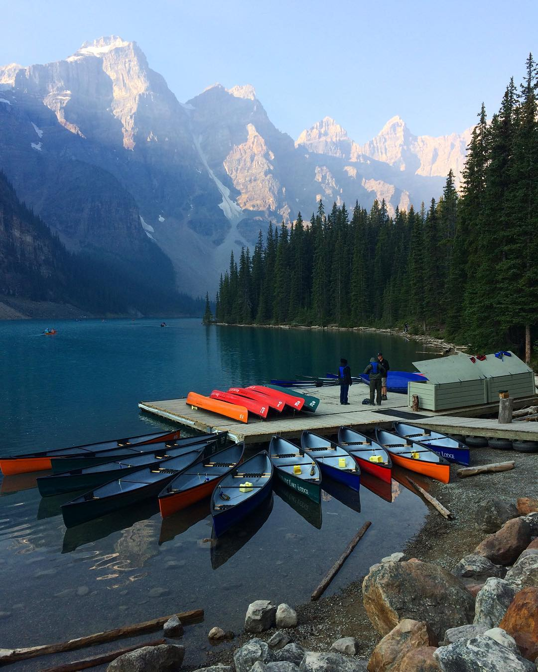 Almost a dozen kayaks are lined around a dock by Moraine Lake nestled among snow capped peaks and forests
