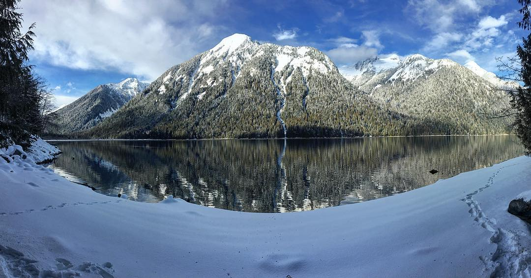 Snow covered mountain by a lake with snow covered ground in the foreground
