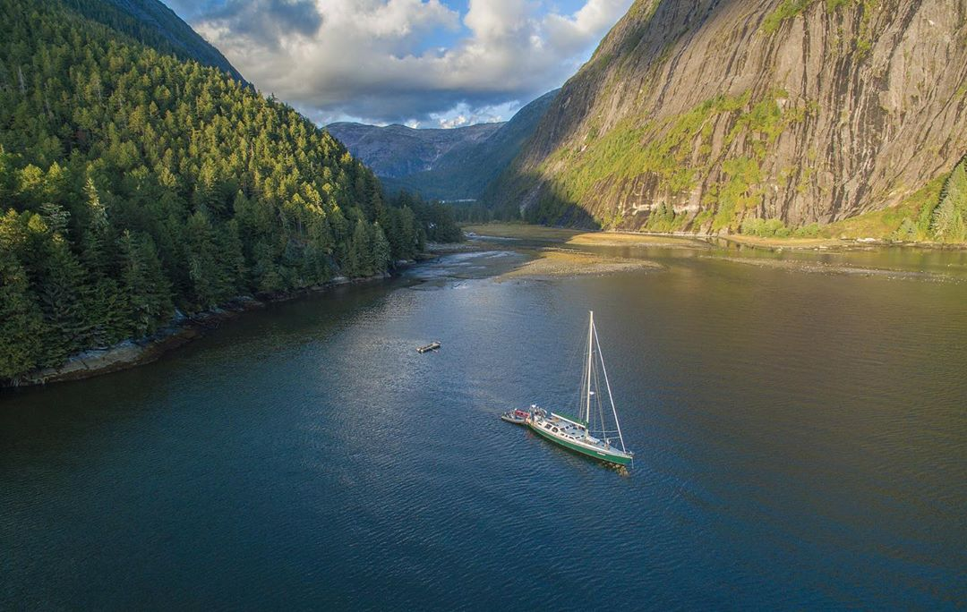 A white sailboat is photographed in the blue waters of ocean between green forested mountains with blue sky and white clouds hovering above