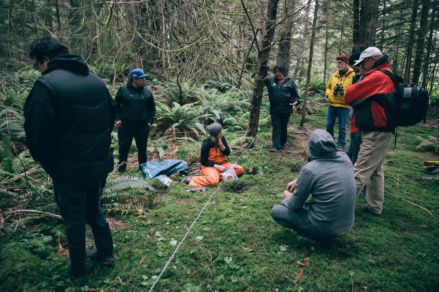 About half a dozen scientists stand or sit around a wire strung across the forest to collect bear hair and samples in the Great Bear Rainforest.