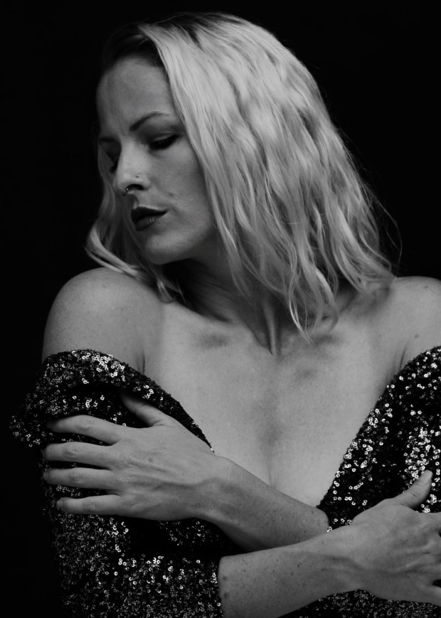 Black and white portrait of woman in sequin dress alone with her thoughts.