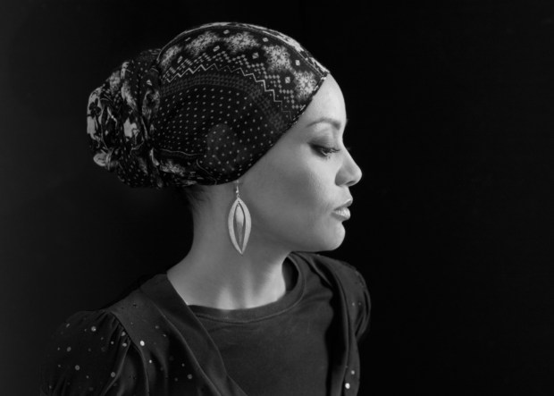 Glamorous black and white portrait of young Muslim woman with head scarf.