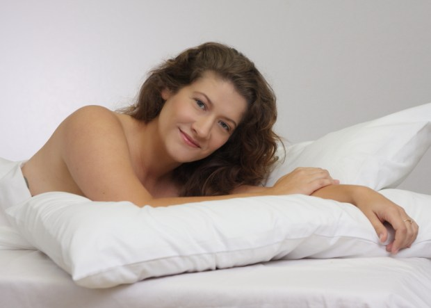 partially nude smiling woman draped in white sheet reclining on a pillow.