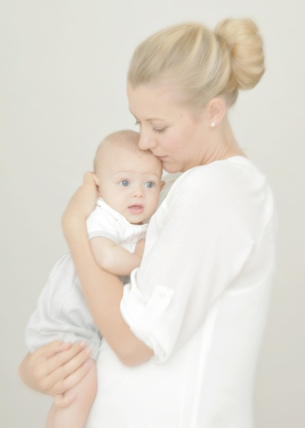 high key portrait of young Alameda mom standing, lovingly holding her baby in her arms.