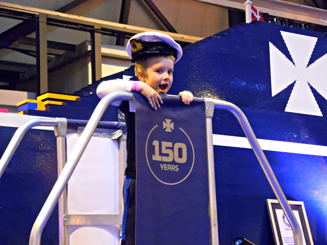 The Little Man with a sailor hat standing in front of the biggest lego ship in the world