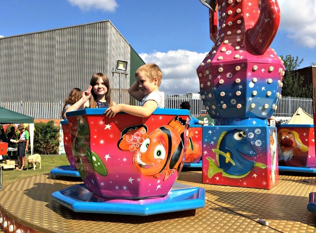 two kids in a teacup ride at the village fete