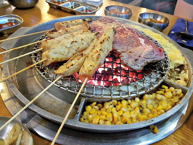 table bbq at Korean restaurant, with chicken and steak cooking over hot coals