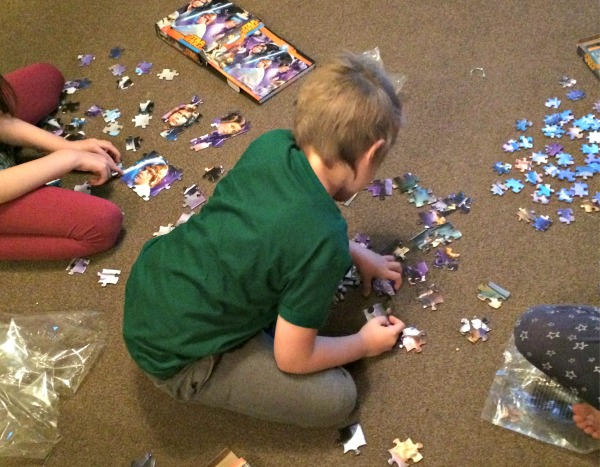 jigsaw puzzle, three children on the floor working on a jigsaw puzzle