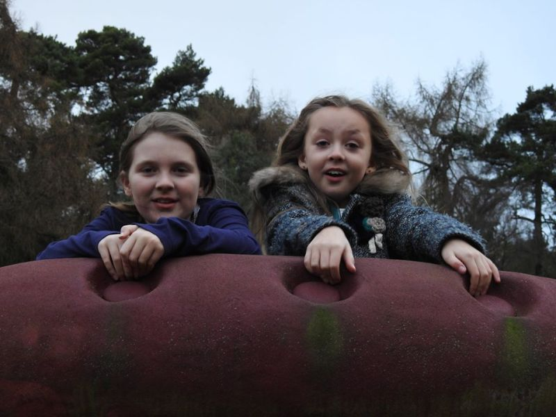 two little girls looking over the back of a huge chair with trees in the background
