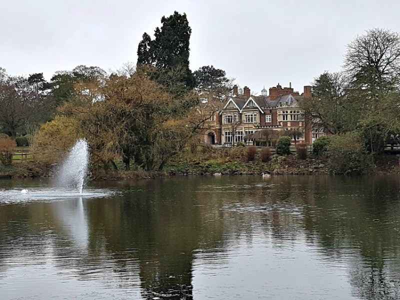 a lake with a small fountain with swans, in the distance, lined by trees you can see the mansion at Bletchley Park
