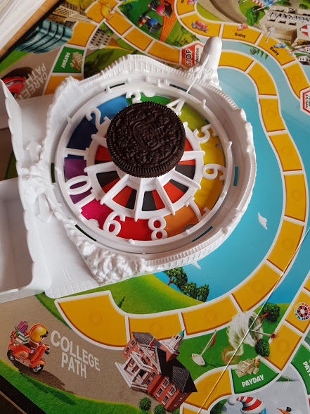 game of life spinner with an oreo on top