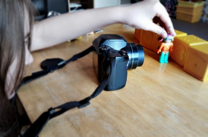 little girl with a camera filming a Roblox figure