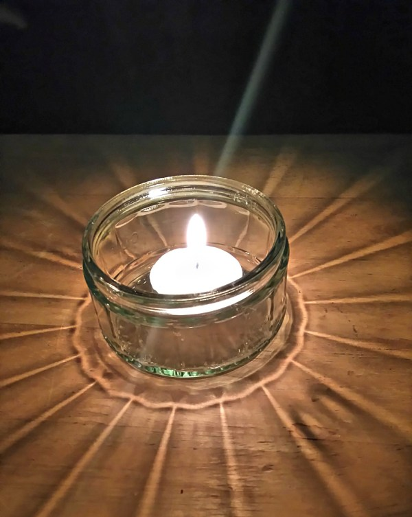 tea light candle in a glass jar spreading light across a table